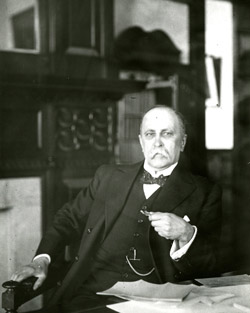 William Osler with letters at his desk.