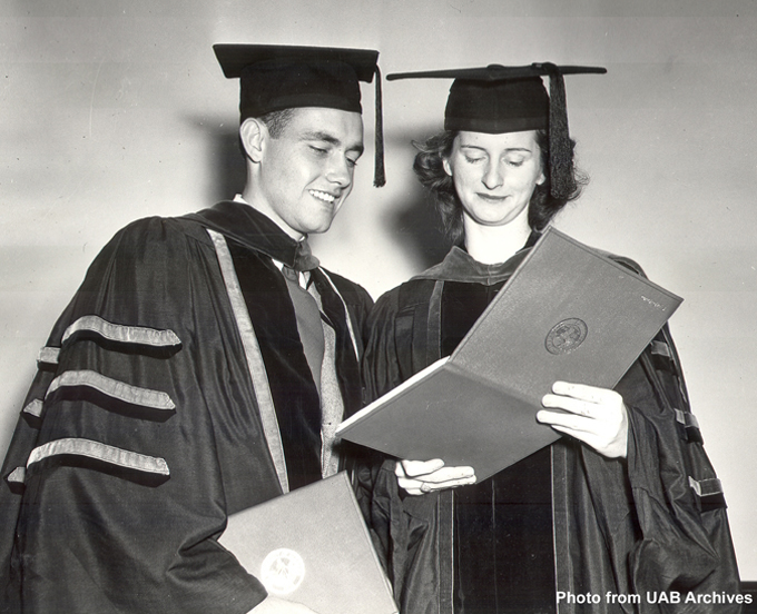 A male and female graduate look at a degree