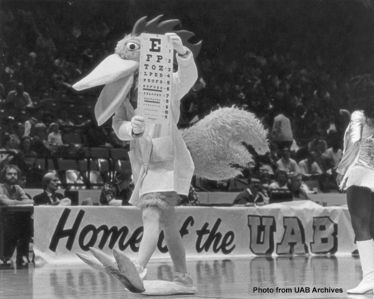 A rooster mascot shows an eye chart to the crowd at a basketball game