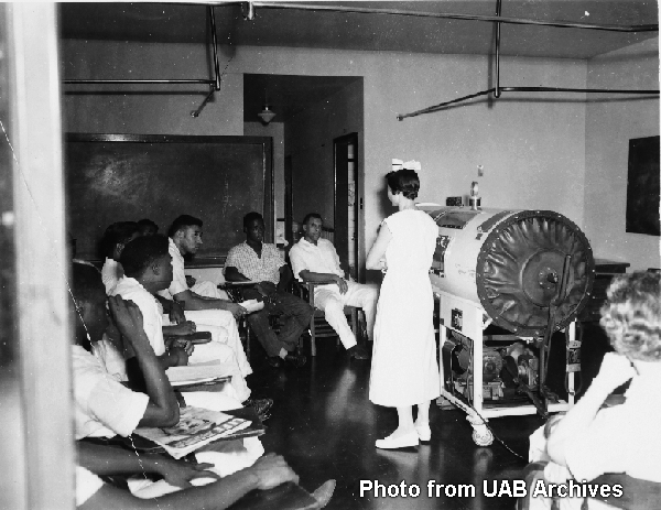 Students listen to instructor in front of an iron lung machine