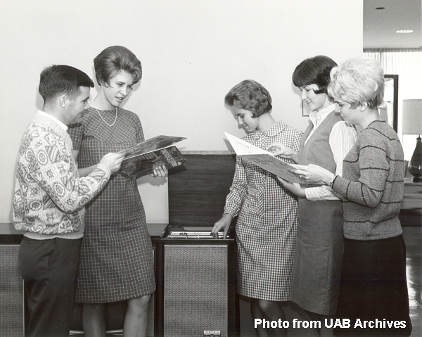 Five students gather, reading pamphlets