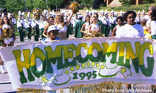 Cheerleaders carry a homecoming banner in front of the band
