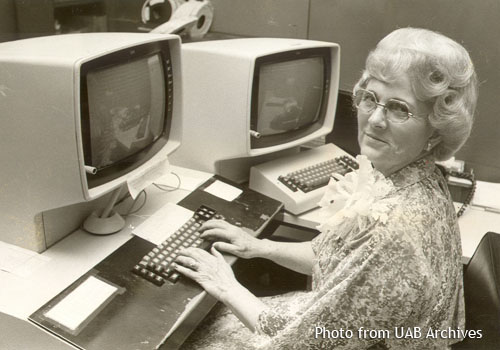A woman sits in front of a computer and looks to the side at the camera
