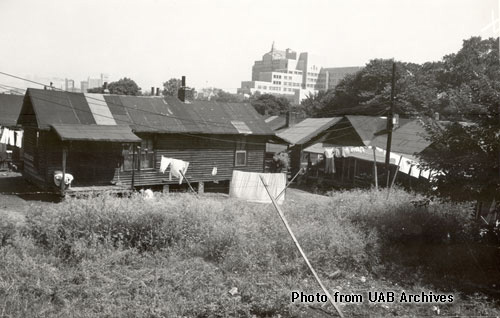 Rundown shack in a field with high rise buildings behind it
