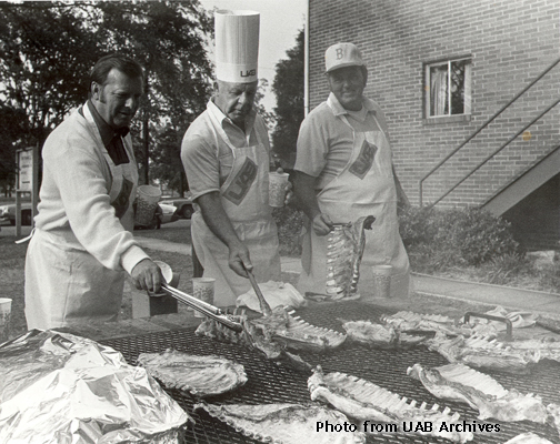 Three men in aprons tend to a bbq pit