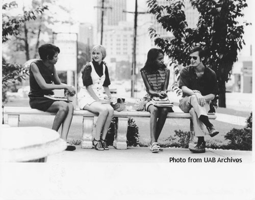 Three women and a man sit on a bench talking