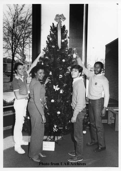 Four students stand in front a Christmas tree, reaching up