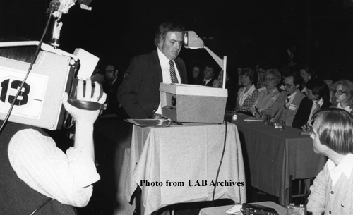A man stands behind a projector with a new camerman watching