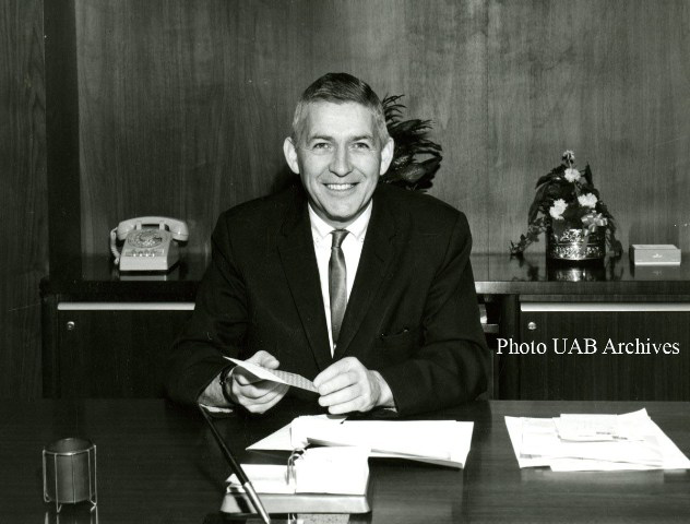 President Volker smiles behind his desk