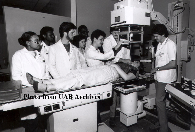 Students look on as a patient is under a radiology machine