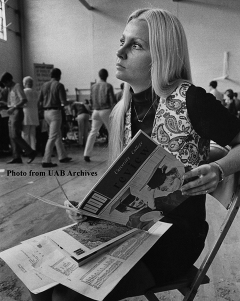 A young female student looks up from a catalog she's holding