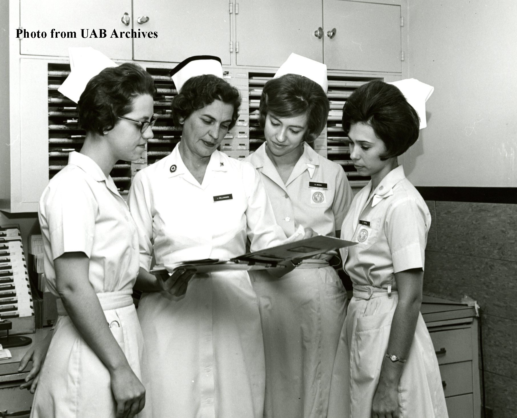 Four female nursing students study a patient chart