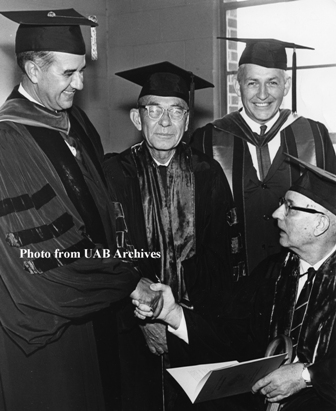 Four men group together in their graduation caps and gowns