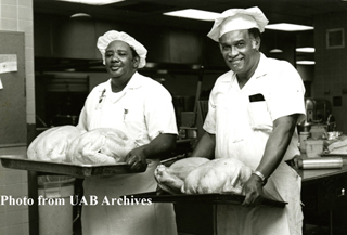 Two male kitchen workers carry turkeys ready to be cooked