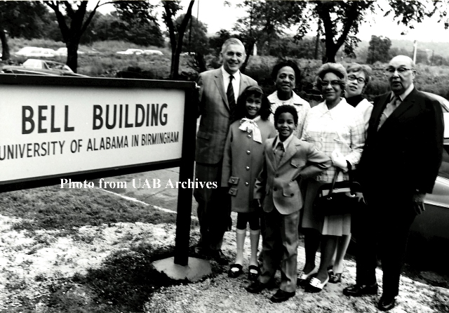 Dr. Volker and the Bell family stand next to the Bell Building sign