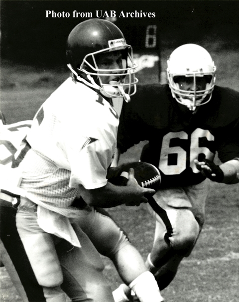 A UAB quarterback runs with the ball with a opponent to his side