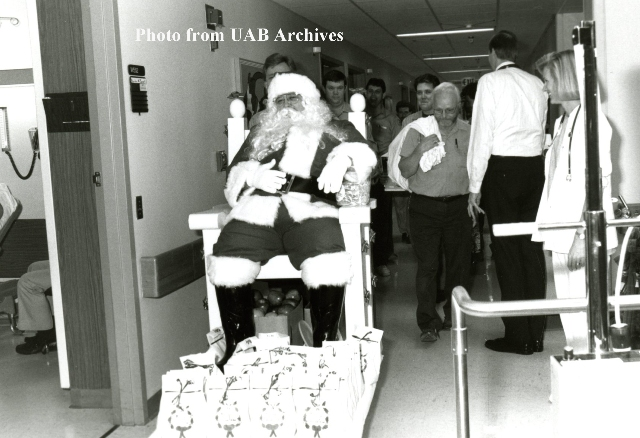 Santa riding on a chair through the hospital hallways