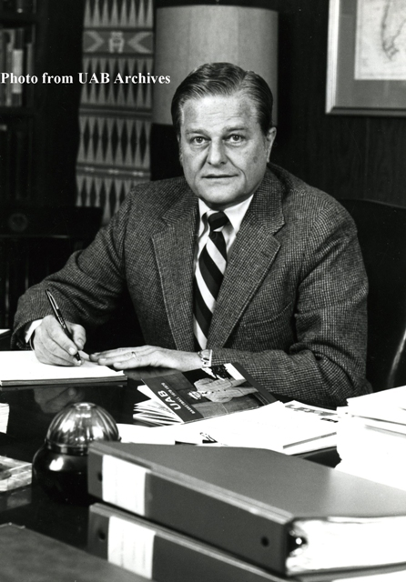 Dr. Hill sits behind a desk, signing a peice of paper