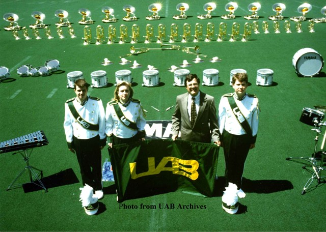 Four members of the UAB marching band stand on a field