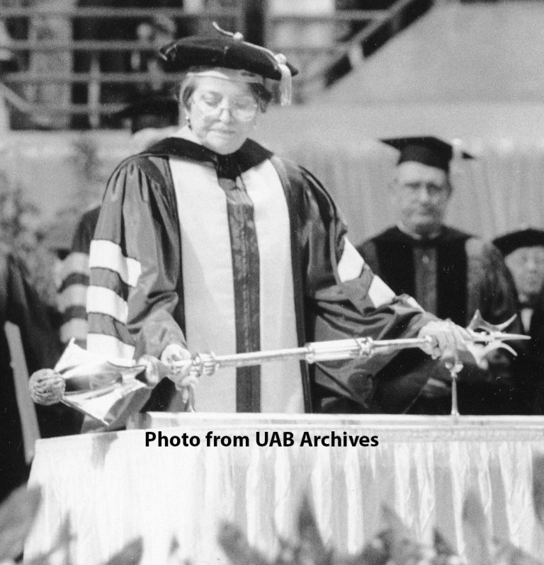 A woman holds a mace at a graduation ceremony
