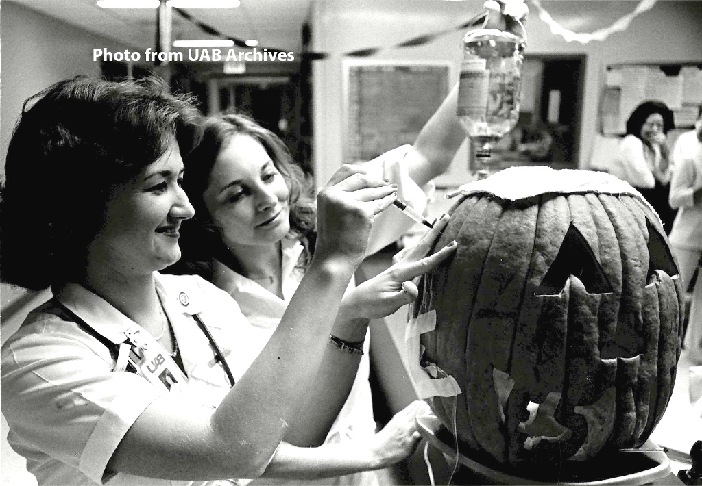 Two women carve a pumpkin