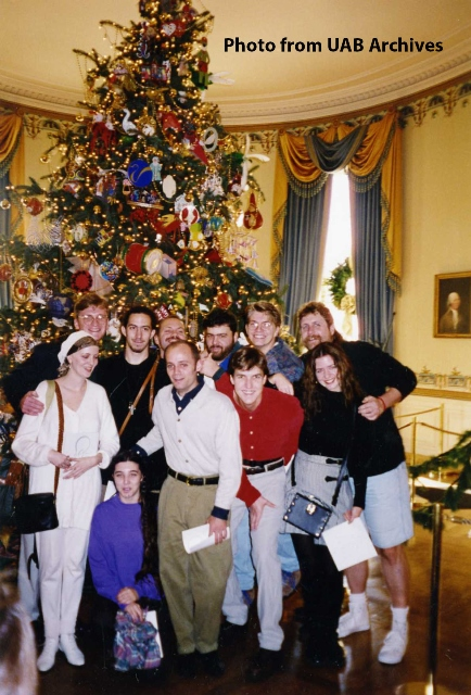 A group of art students pose in front of a Christmas tree in the White House