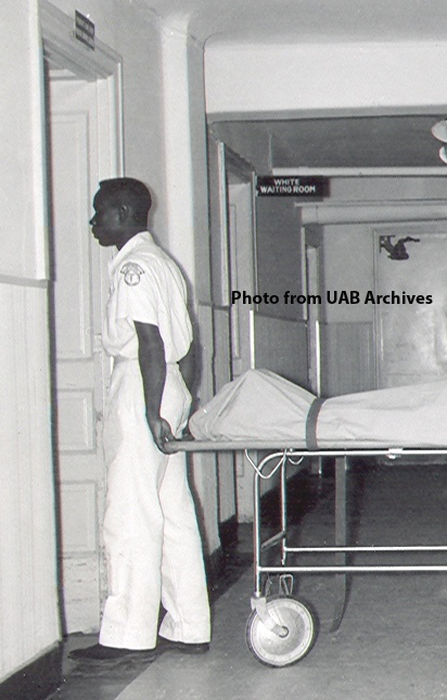 An African American hospital worker pulls a gurney into a room