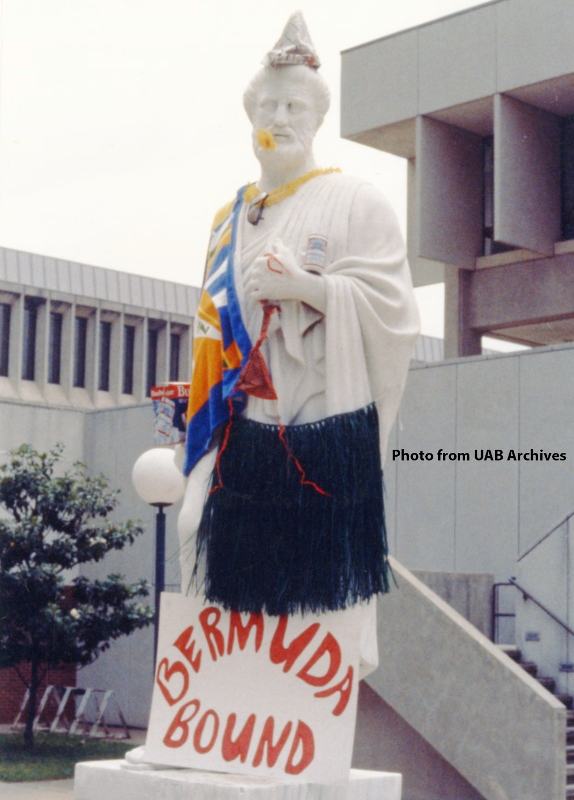 Hippocrates statue dressed in a blue grass skirt with a Bermuda bound sign
