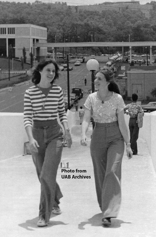 Two female students walk across the pedestrian bridge