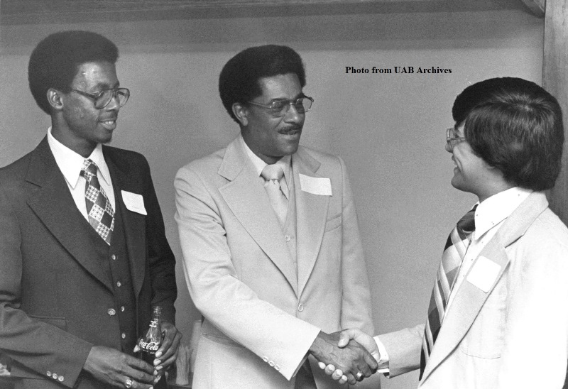 Aaron L. Lamar, Jr. shakes hands with a student while another student looks on
