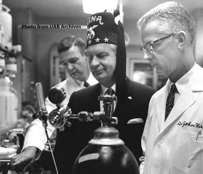 A shriner stands between two physicians examining equipment