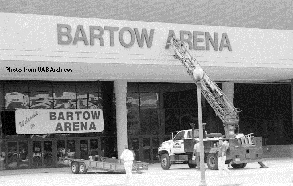 A ladder extends up from a truck to the Bartow Arena sign