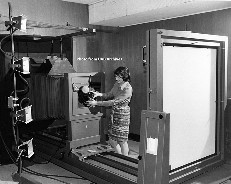 A woman adjusts a large process camera
