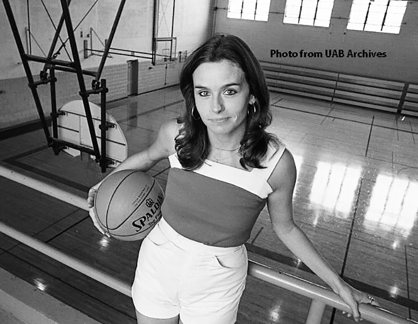 Fran Sharp Merrell poses with a basketball above the court