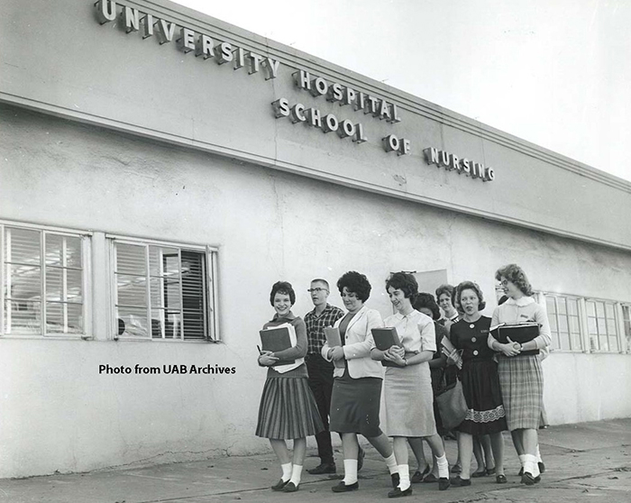 A group of students walk in front of the University Hospital School of Nursing